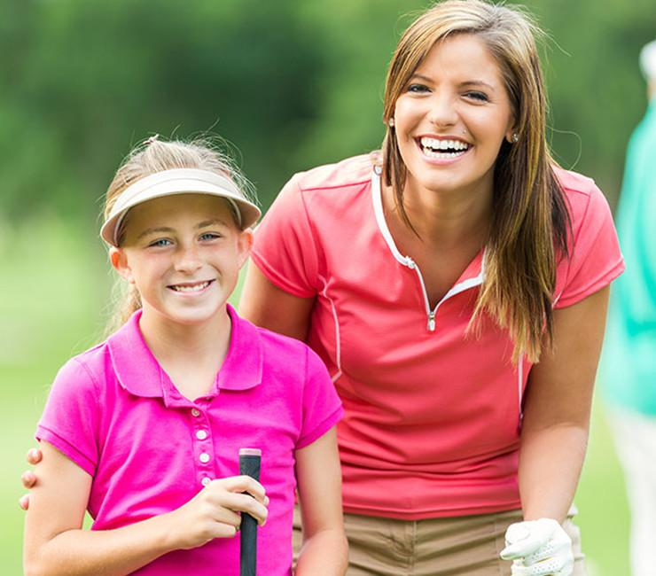 Woman and child holding golf clubs