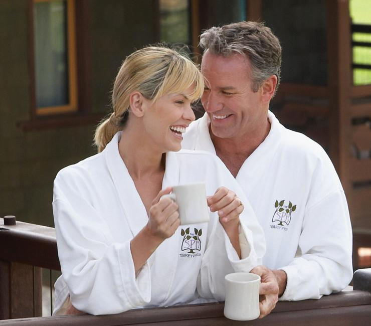Guests at The Lodge at Torrey Pines enjoying a morning coffee on their deck wearing luxury robes, part of the luxury room amenities at this five diamond resort in La Jolla, CA.