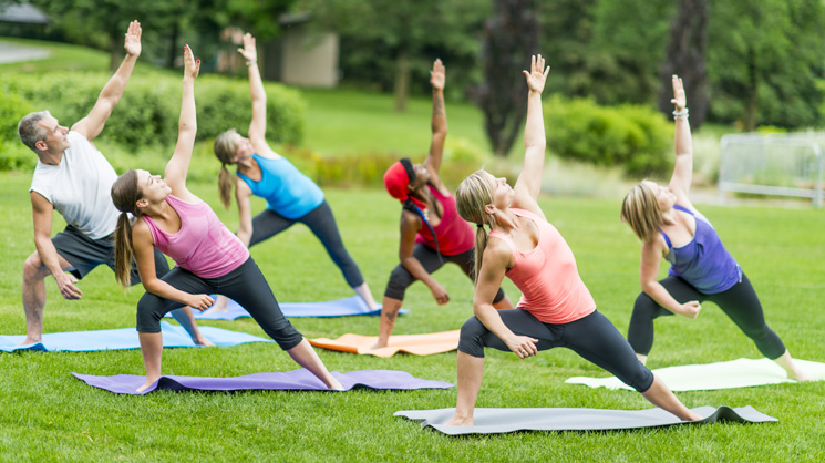 Group of people enjoying yoga outdoors