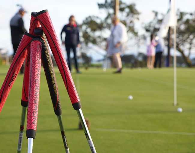 Putter handles in foreground and people in background