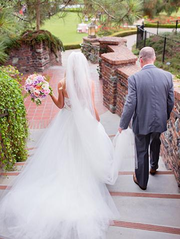 Father walking with bride on brick staircase at The Lodge at Torrey Pines